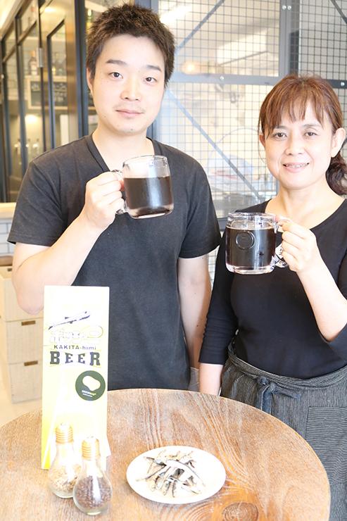 完成した煮干しビールを手にする山本さん(左)と柿谷さん=氷見市比美町のブルーミン