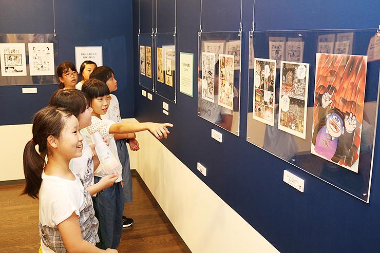 ブラックユーモアをテーマに新たに展示された複製原画に見入る児童=氷見市潮風ギャラリー