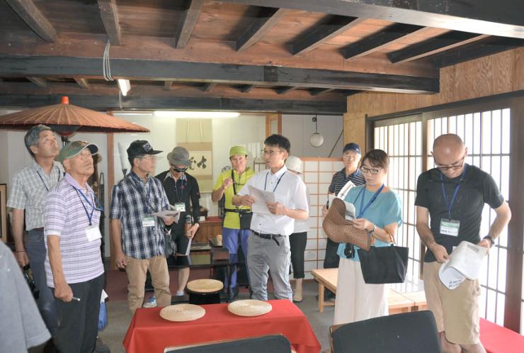 須坂市中心街に残る古い住宅について土本教授(手前右から3人目)の説明を聞く「町並み探索」の参加者=14日