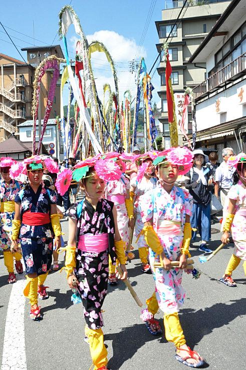 色とりどりの幟(奥)と着飾った児童らが練り歩いた岳の幟