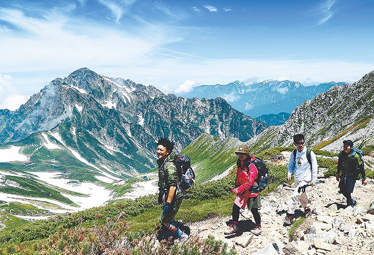 別山乗越へ向かうりょう線を歩く登山者。奥には剱岳(左)や後立山連峰が広がる =別山近く