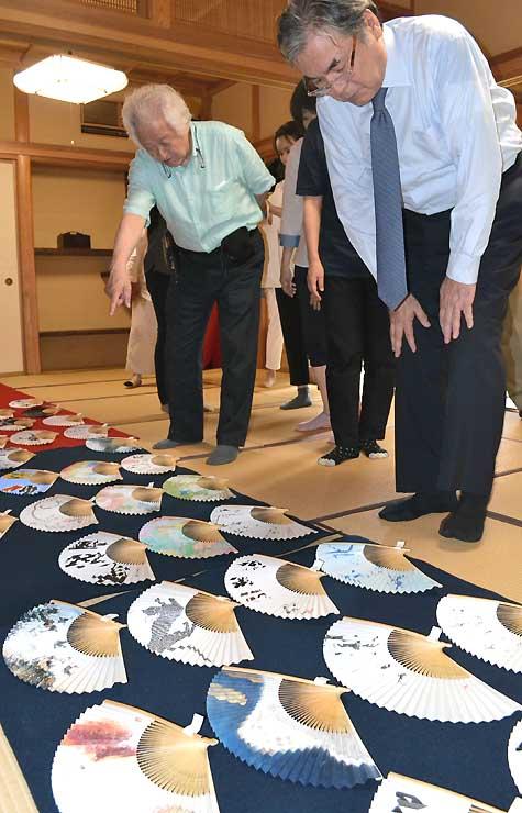 県内外から集まった扇子を審査する高木さん(右)と土屋さん