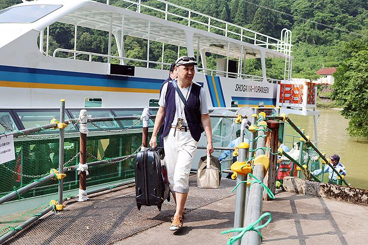 大牧発電所の船着き場で遊覧船から降りる乗客=南砺市利賀村大牧