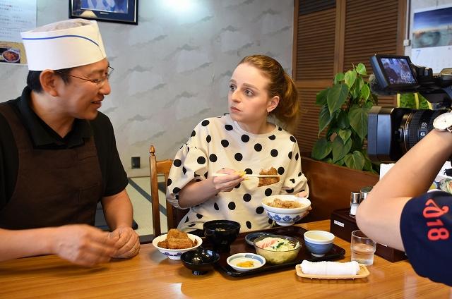 ヨーロッパ軒総本店のソースカツ丼を食べながら、おいしさの理由を取材するクラスマンさん(中央)=福井県福井市順化1丁目
