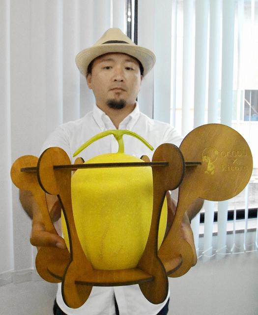 越前箪笥の技術を使ったケースに入ったメロンをPRする岡田英明さん=7月17日、福井県坂井市内