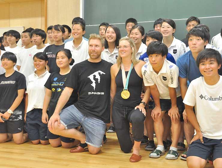 金メダルを掛け、飯山高校スキー部員らと記念撮影するシャープ選手(中央)