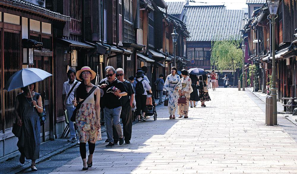 日差しを避け日陰を歩く観光客=金沢市のひがし茶屋街