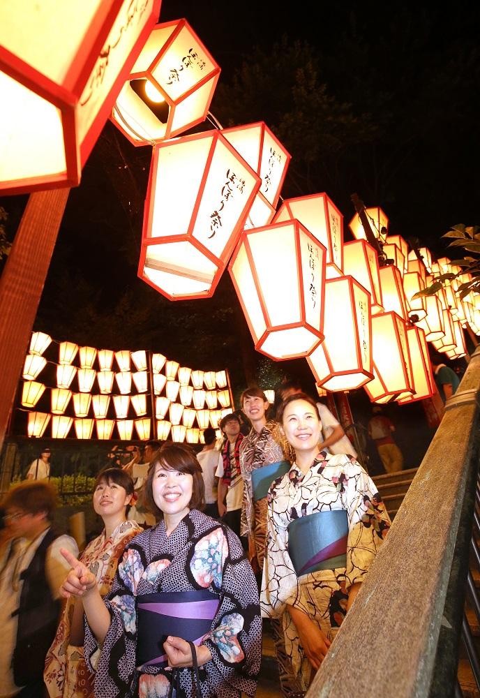 幻想的に光るぼんぼりに見入る来場者=金沢市の湯涌温泉