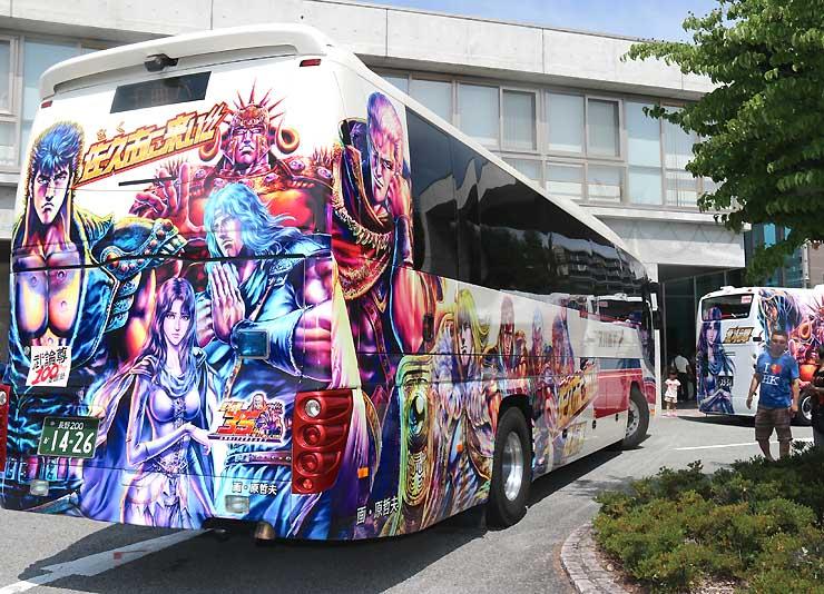 北斗の拳のキャラクターがデザインされた高速バス。右奥は市内循環バス