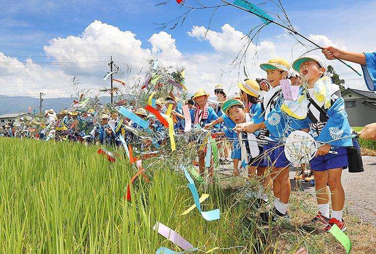 田んぼに向かって「ねつおくるばーい」とササ竹を振る子どもたち=南砺市荒木