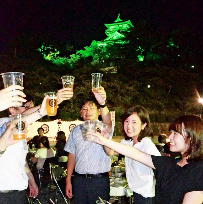 ライトアップされた丸岡城天守を背に乾杯する来場者=20日夜、坂井市のお天守前公園