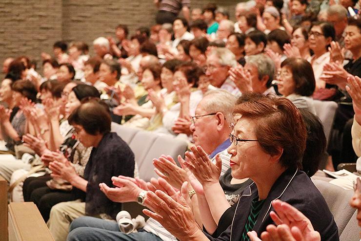 映画「百年の蔵」の神監督に拍手を送る来場者=新川文化ホール