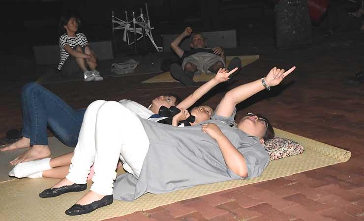 星空観望会であおむけになって星を眺める人たち