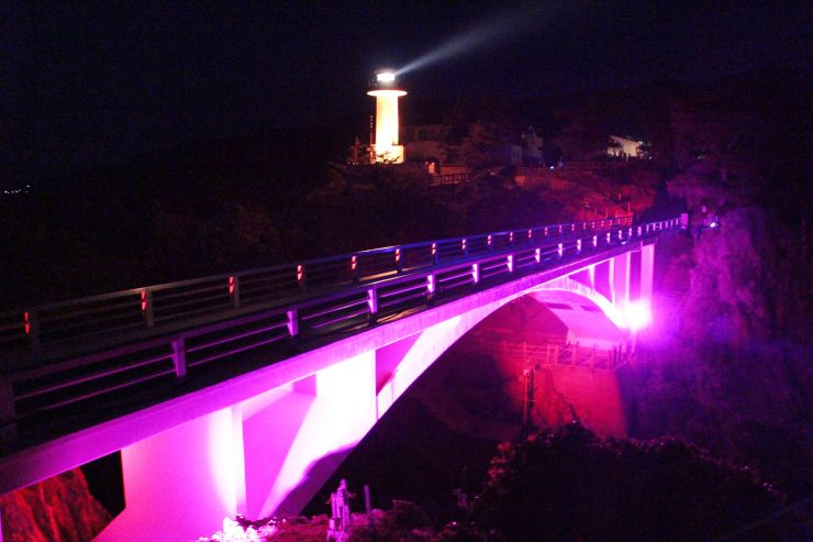 ライトアップで暗闇に照らし出された遊仙橋と灯台=いずれも佐渡市北狄