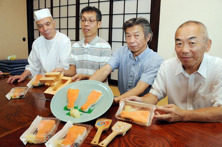 鳴子をモチーフにした「鳴子寿司」を手にする関係者