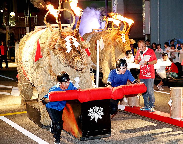 たいまつを付けたわら製の火牛を走らせた「火牛の計レース」=石動駅前商店街