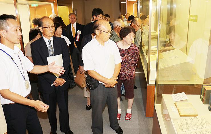 近藤学芸員(左)の解説を聞きながら、貴重な資料に見入る来館者=滑川市立博物館