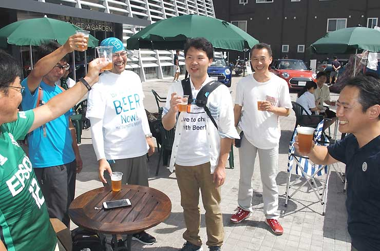松本ブルワリーのビールで乾杯する客らと林社長(右)