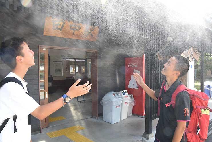田中駅の入り口に設置されたミストシャワー。高校生らが霧状の水を浴びながら涼んでいる