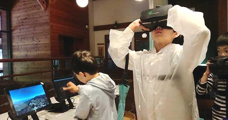 VRゴーグルを装着して奥穂高岳からの光景を疑似体験する子どもら