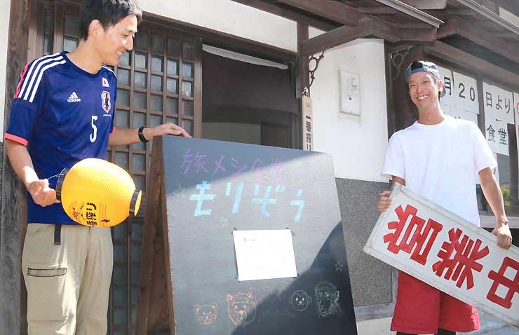 食堂の玄関で看板を手にする大森さん(左)と中島さん