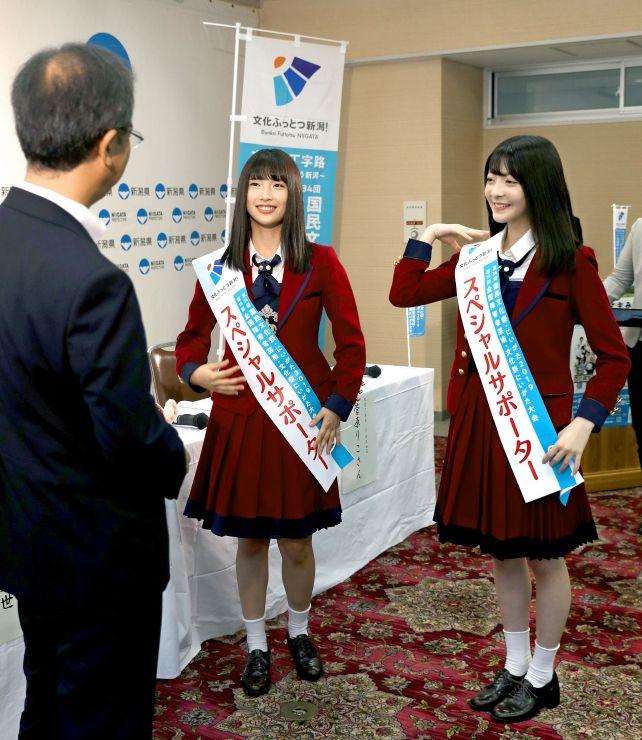 スペシャルサポーターのたすきを掛けるNGT48の佐藤杏樹さん(中)と菅原りこさん(右)=7月31日、県庁
