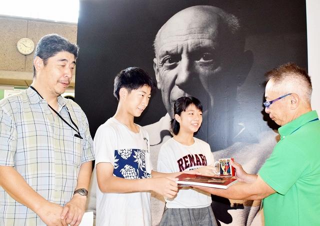 ピカソ展1万人の記念品を贈られる親子=8月2日、福井県立美術館