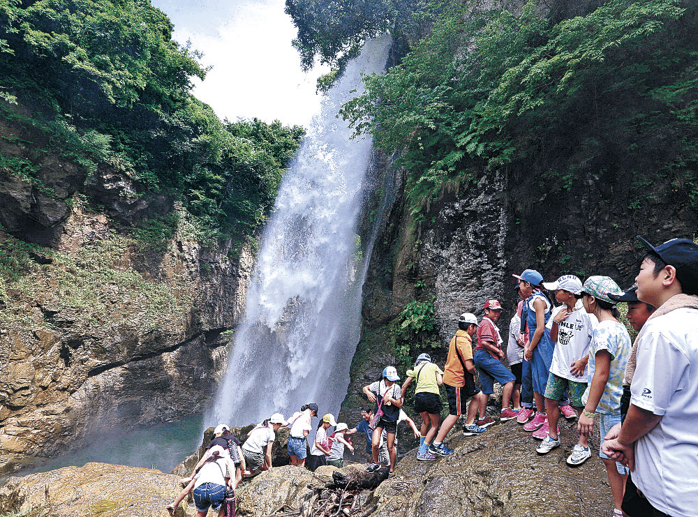 滝の近くで水しぶきを浴びて涼む児童=白山市下吉谷町