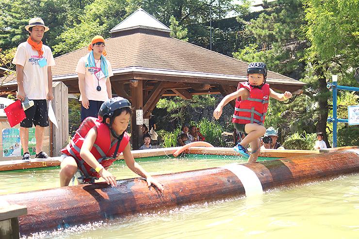 丸太の上で熱戦を繰り広げる児童=庄川水記念公園前