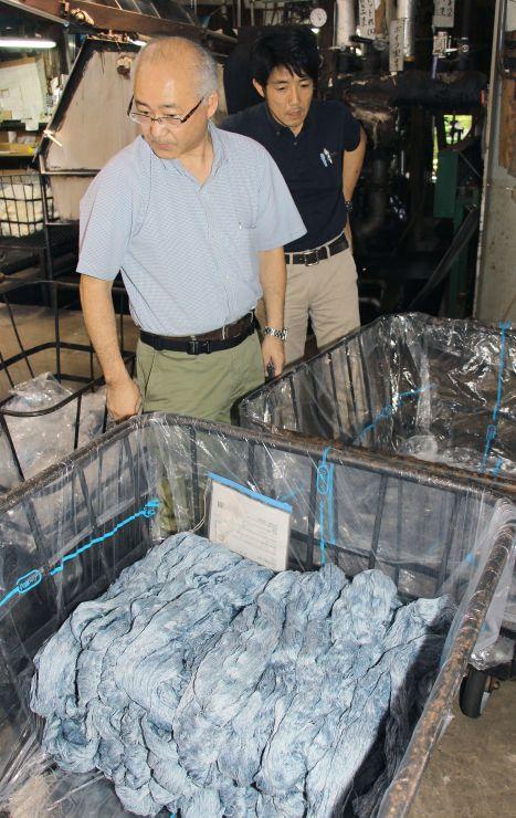 染め上がった糸を確認する港屋の星野善彦社長(左)と星野貴宏専務=長岡市東町の港屋