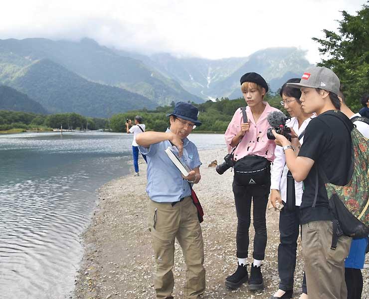 北アルプス上高地の大正池でガイド(左)の説明を聞く香港の旅行雑誌スタッフら