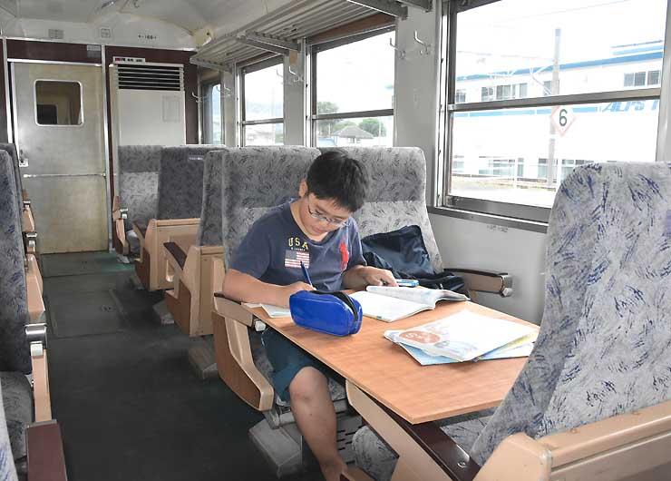 169系車両内で勉強する小学生。冷房も効いてはかどりそう