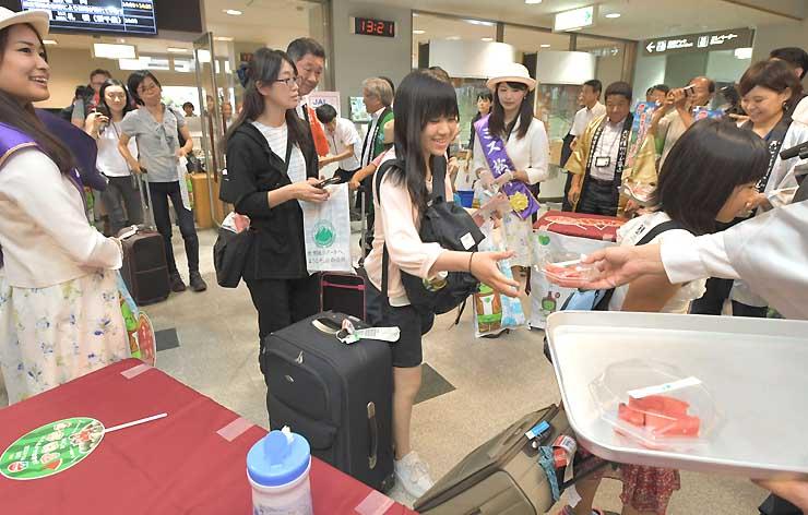 札幌丘珠空港から到着後、歓迎を受けて記念のスイカをもらう利用客=8日、松本市の県営松本空港