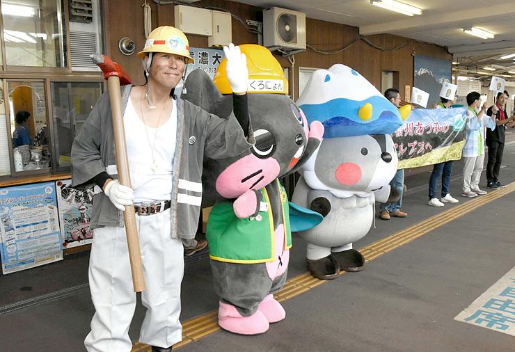 JR信濃大町駅のホームで観光客を出迎えた「岩岡剛」(左)とキャラクターたち=11日
