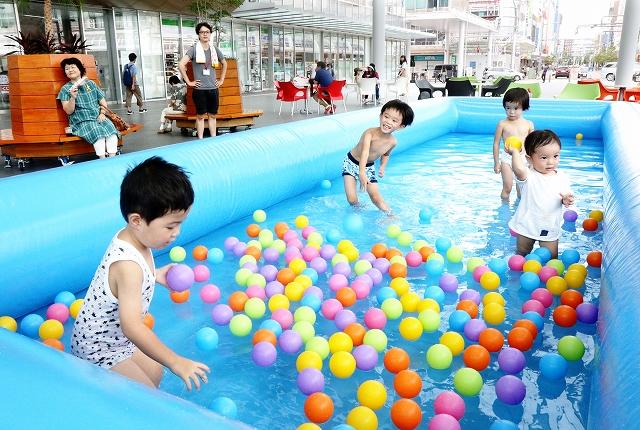 ハピテラスに設けられたプールで水遊びを楽しむ子どもたち=8月13日、福井県福井市中央1丁目