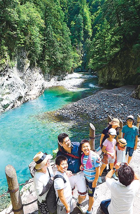 清流・黒部川の流れや木々の緑など峡谷美を楽しむ観光客=欅平