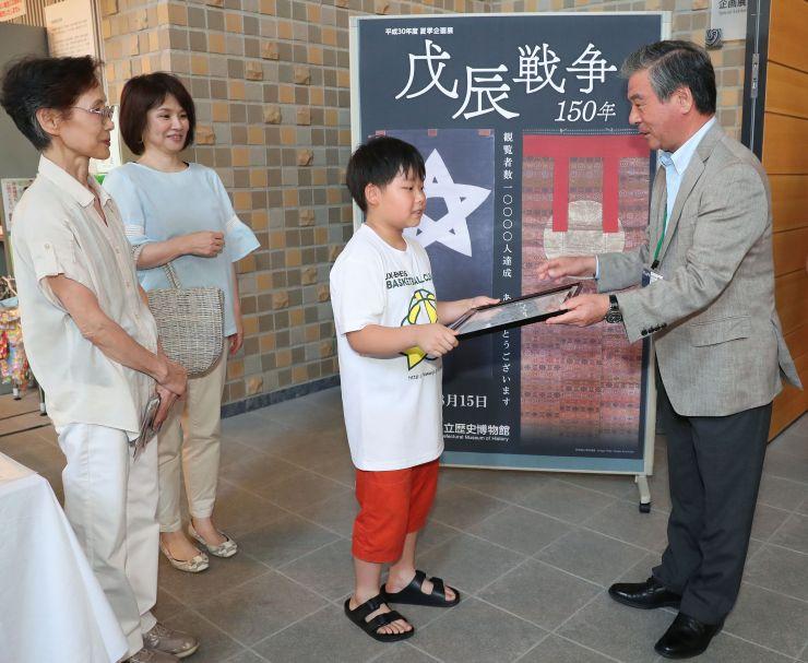 1万人目の記念品を受け取る男子児童(右から2人目)=15日、長岡市関原町1