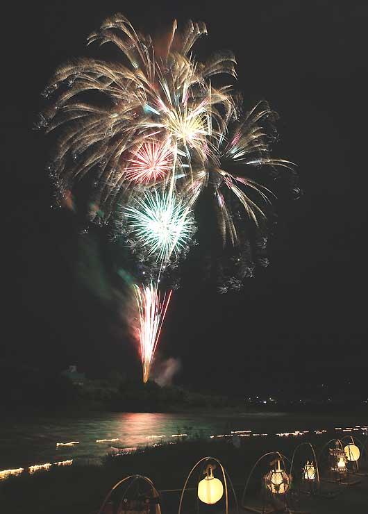 灯籠が流れる天竜川の上空を、打ち上げ花火が彩った=16日午後7時31分、飯田市