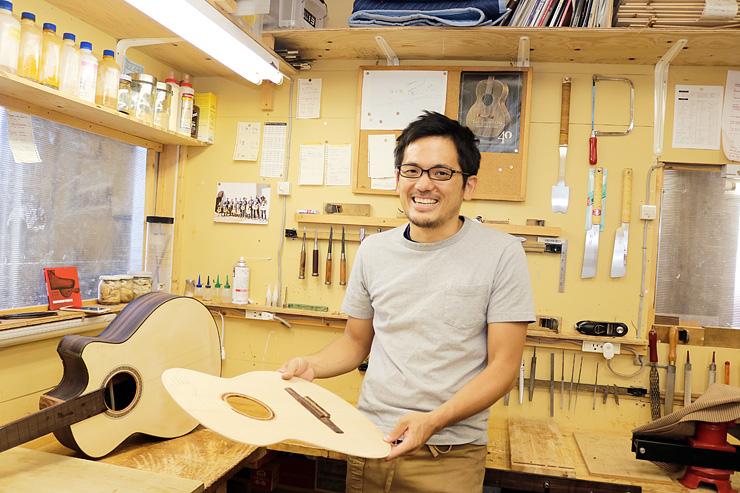 製作中のギターを手に「富山ならではのものを作りたい」と話す藤井さん=富山市今市の工房