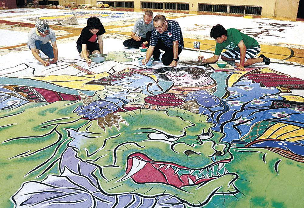 武者絵を制作する太田さん(右から2人目)と住民=能登町の旧鵜川小体育館