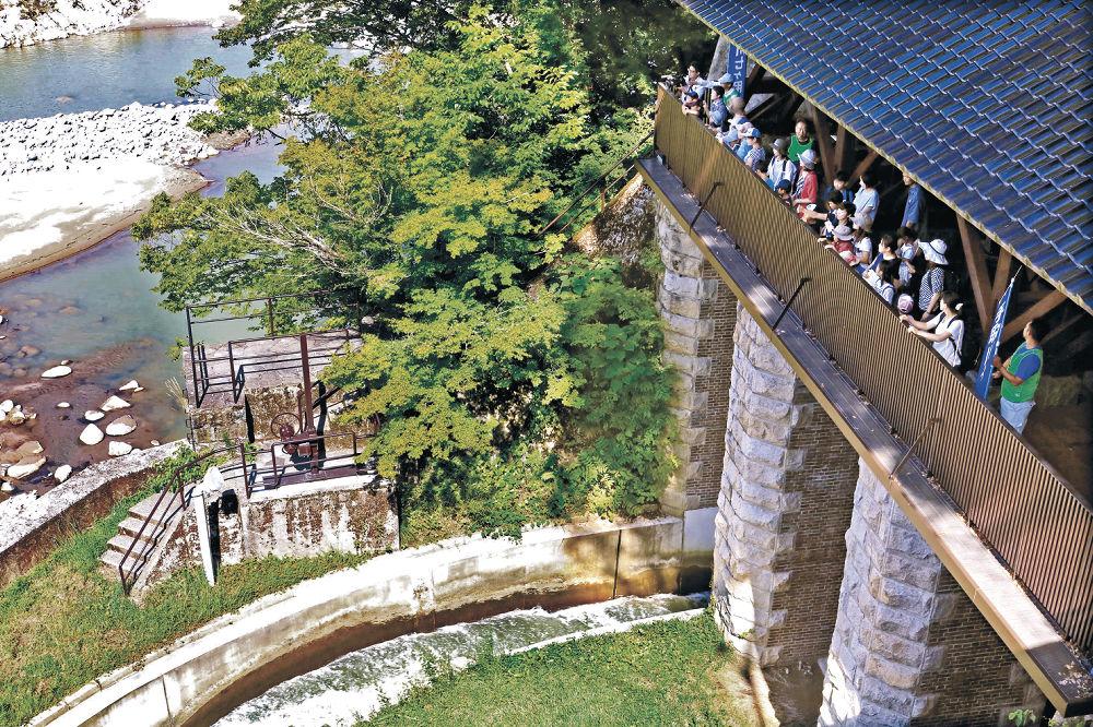 七ケ用水の大水門を見学する参加者=白山市白山町