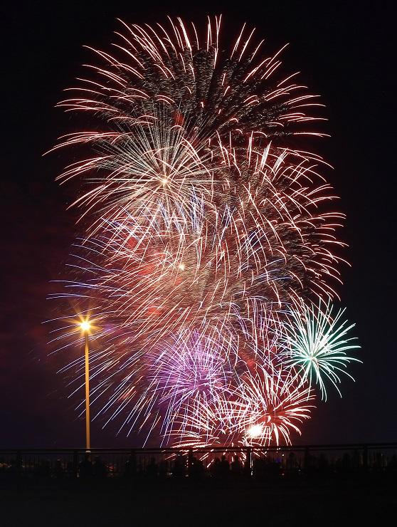 明神橋の上空を彩る打ち上げ花火=18日午後7時23分、高森町