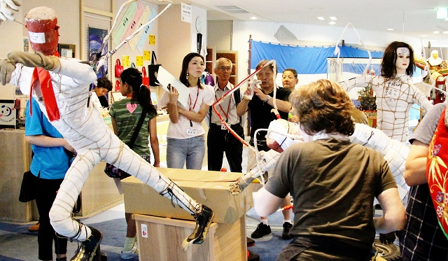 武者人形の飾り付け作業を見学する参加者=8月19日、福井県敦賀市みなとつるが山車会館