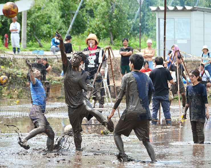 全身泥だらけになりながらバレーボールを楽しむ人たち