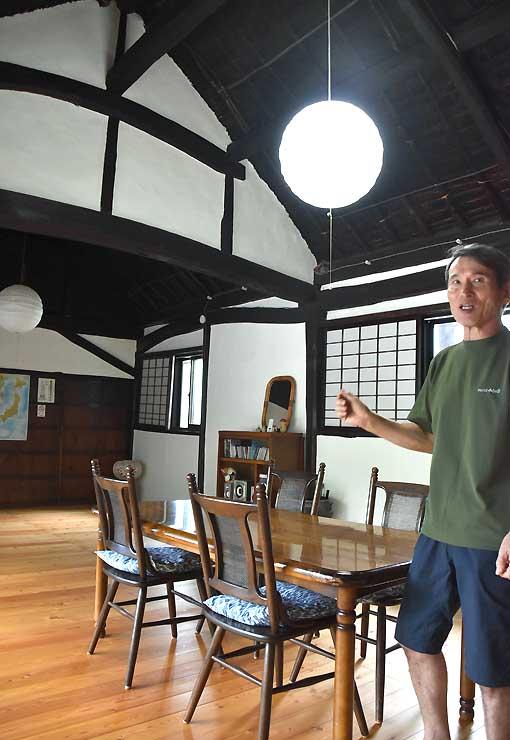 ゲストハウスのリビングを紹介する前田守さん