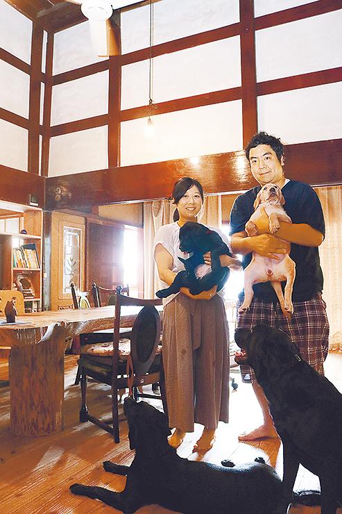 望頼山荘で犬を抱き笑顔を見せるマクニコルさん(右)と足立さん