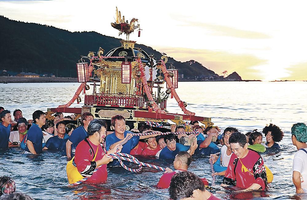 豊漁を願い、神輿を担いで海に入る若衆=輪島市の袖ケ浜海岸