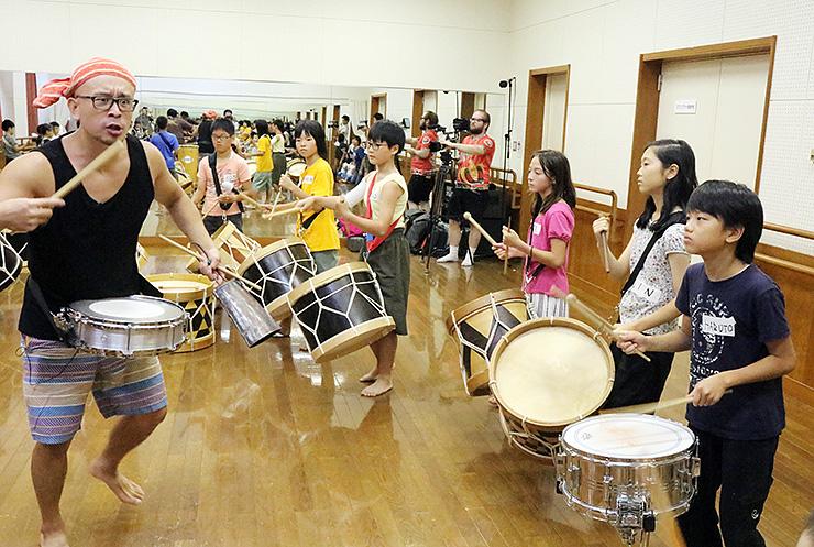 廣瀬さん(左)と共に太鼓を打ち鳴らす子どもら