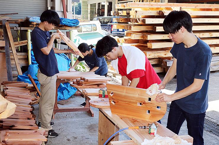 ベンチやテーブルの加工作業に取り組む学生ら=長田組