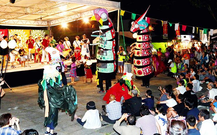 巨大人形と共に躍動のステージを繰り広げた「トゥーマラッカ」のメンバーら=南砺市福野文化創造センター